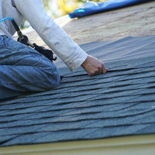 A Roofer Installs Shingles.