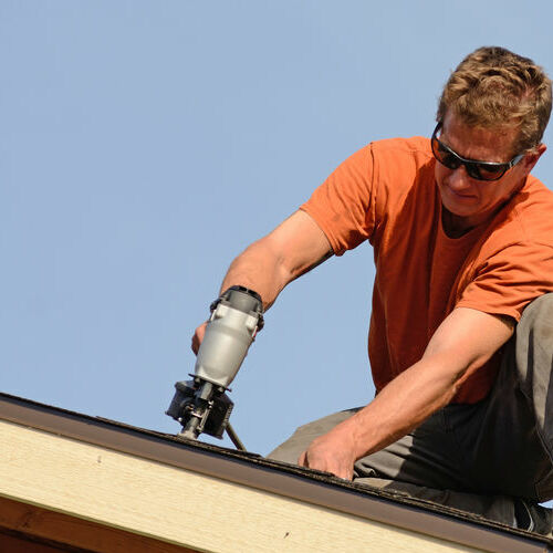 A Roofer Installs New Shingles.