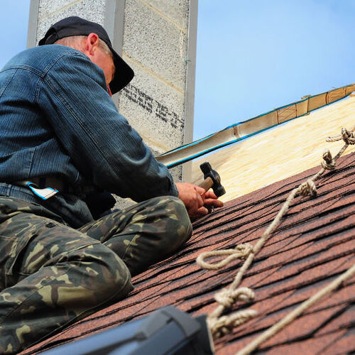 A Roofer Repairs Shingles.